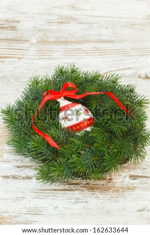 Christmas wreath and ornaments over old wooden  background. Copy space composition - stock photo