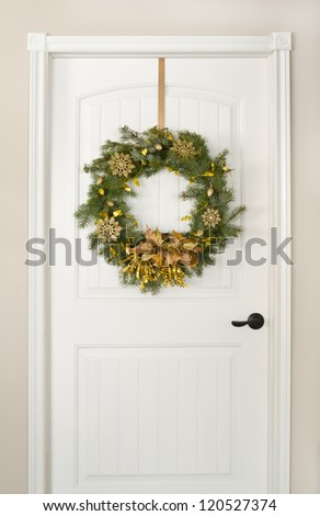 Christmas wreath, decorated in gold on a white door - stock photo