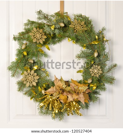 Christmas wreath decorated in gold on a white door - stock photo