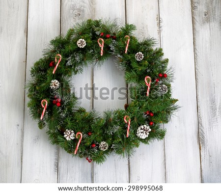 Christmas wreath decorated with pine cones, candy canes, and red berries on rustic white wooden boards.