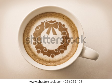 Christmas wreath drawing on latte art coffee cup top view - stock photo
