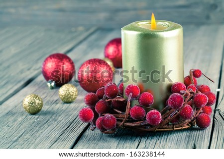 Christmas wreath from red berries with a candle on wooden background - stock photo