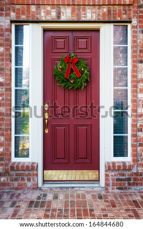 Christmas wreath hanging on a red wooden door of a brick house  - stock photo