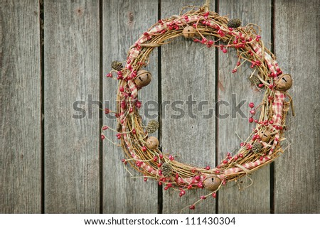 Christmas wreath hanging on a wooden rustic vintage background with copy space - stock photo
