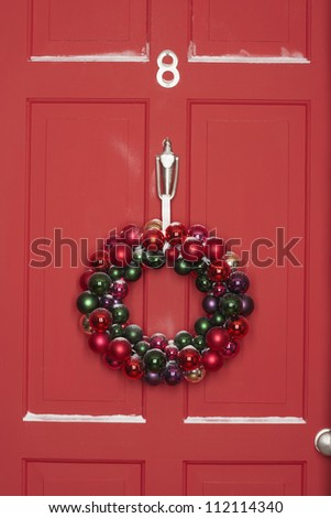 Christmas wreath hanging on door - stock photo