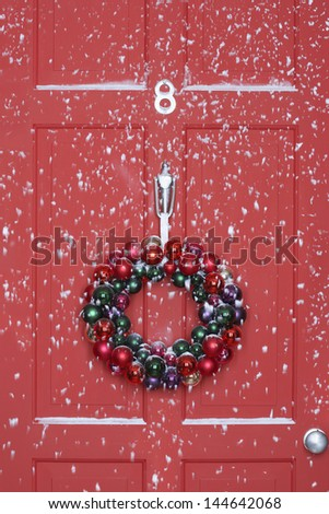 Christmas wreath hanging on door with snowfall - stock photo
