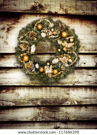 Christmas wreath hanging on wooden wall - stock photo