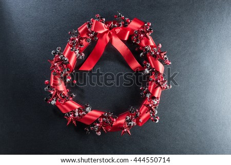 Christmas wreath in red with ribbon over plain color background