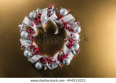 Christmas wreath in red with silver ribbon over plain color background