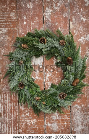 Christmas wreath made from pine twigs ornamented with pine cones on wooden table - stock photo