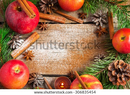 Christmas wreath made of fir branches, cones, red apples and cinnamon. Copy space background - stock photo