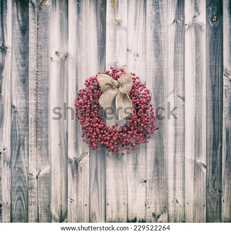 Christmas wreath made of holly berries tied with a burlap bow hangs on an old weathered wood wall. Vintage filters applied.  - stock photo