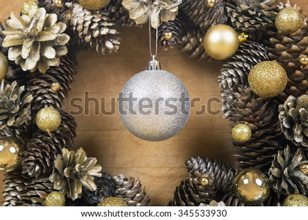 Christmas wreath of cones with silver ball in the center on wooden background close-up.  - stock photo