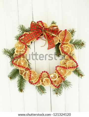 christmas wreath of dried lemons with fir tree and bow, on white wooden background - stock photo