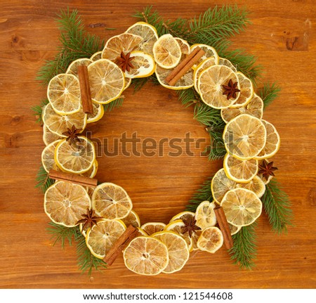 christmas wreath of dried lemons with fir tree on wooden background - stock photo