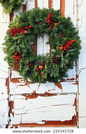 Christmas wreath of  evergreen and red holly berries against a vintage wooden door. - stock photo