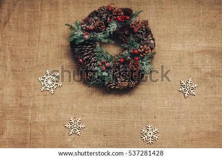 Christmas wreath of fir branches, cones and red berries lies on sacking next to wooden snowflakes.