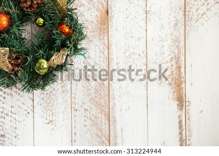 Christmas wreath of fir tree is hanging on white wall. There are many varicolored toys and cones on decoration. Copy space in right side - stock photo