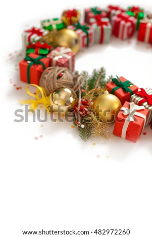 Christmas wreath of gifts, fir branches and balls. White background. Small handmade gifts in red, green and gold paper.