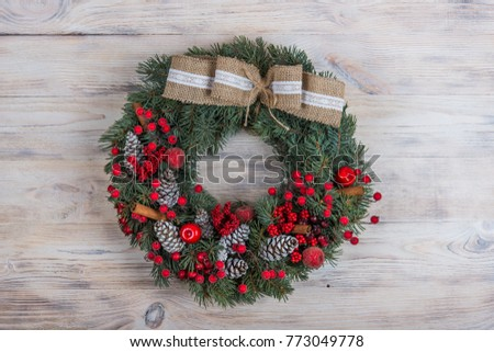 Christmas wreath of pine with red elements on a white wooden background. Christmas winter frame.
