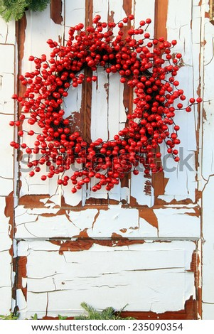 Christmas wreath of red holly berries against a vintage wooden door.  - stock photo