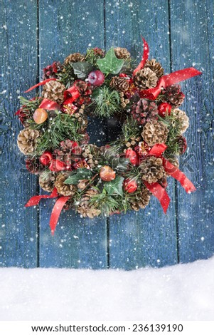 Christmas wreath on a green rustic door with falling snow - stock photo