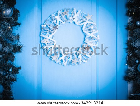 Christmas wreath on a rustic wooden front door. Blue toned - stock photo