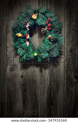 Christmas wreath on a rustic wooden wall with copy space.  Retro vintage effect. - stock photo