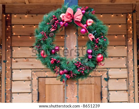 Christmas Wreath on natural wood doorway with strings of lights