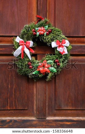 Christmas wreath on the wood red door - stock photo