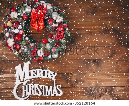 Christmas wreath on the wooden background with snow
