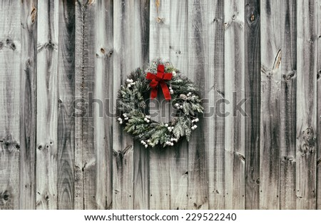 Christmas wreath tied with a red velvet bow is sprinkled with snow, made of pine branches, berries and pine cones and hangs on a weathered plank wall.  Vintage filter applied.  - stock photo