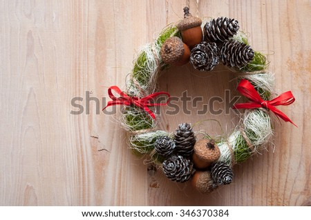Christmas wreath with acorns, pine cones and red bows. On wooden background.