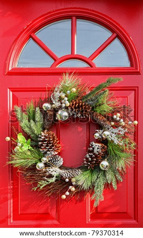 Christmas wreath with baubles, cones and evergreen boughs on a red door. - stock photo