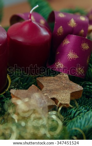 Christmas wreath with candles, decor and ribbons - stock photo