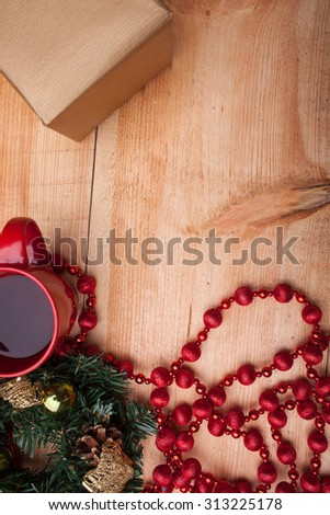 Christmas wreath with cones and toys near a red cup of coffee. The decoration with small box of gift is situated on wood background - stock photo