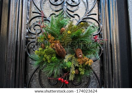 Christmas wreath with cones hanging on a door - stock photo