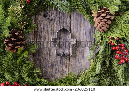 Christmas Wreath with Ginger man Cookie in the Middle of Wood Background - stock photo