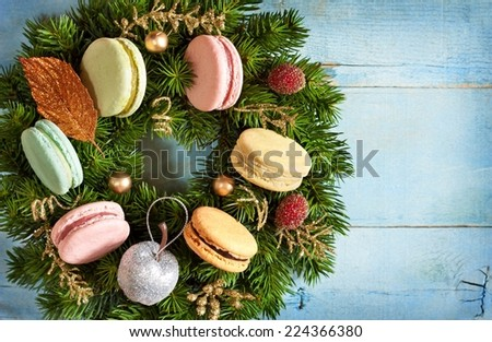 Christmas wreath with macarons cakes and decorations on an old blue wooden board. Christmas card. Vintage style. - stock photo