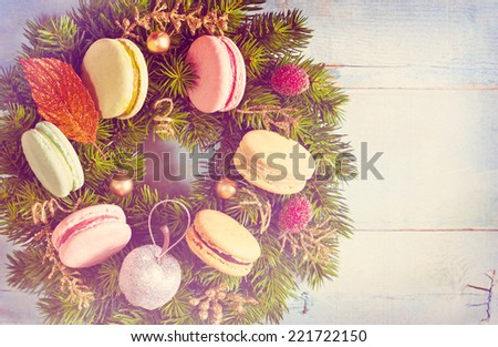 Christmas wreath with macarons cakes and ornament on an old blue wooden board. Christmas card. Vintage toned photo. - stock photo