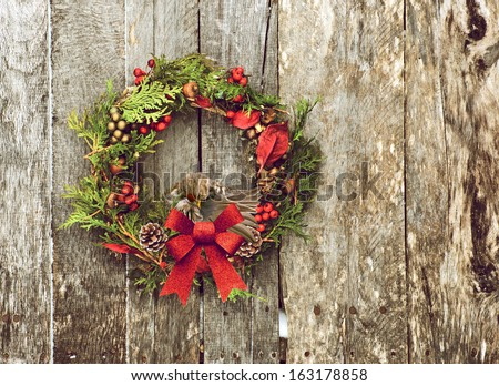 Christmas wreath with natural decorations with a beautiful common redpoll bird perched, preening her feathers, hanging on a rustic wooden wall with copy space.  - stock photo