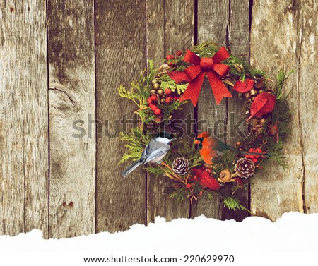 Christmas wreath with natural decorations with a beautiful male Northern Cardinal peeking out, and a cute chickadee perched,  hanging on a rustic wooden wall with copy space.  Photo illustration.  - stock photo