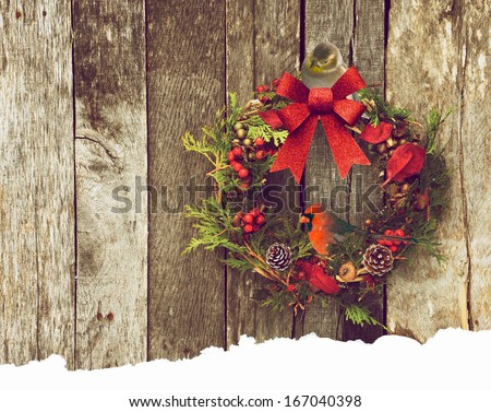 Christmas wreath with natural decorations with a beautiful male Northern Cardinal perched, with a pretty goldfinch peeking down at him from behind the bow, hanging on a rustic wooden wall.  - stock photo