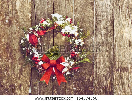 Christmas wreath with natural decorations with a beautiful male pine siskin bird perched, hanging on a rustic wooden wall with copy space.  - stock photo