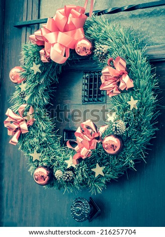 Christmas wreath with pine cones, pink bows, balls and golden stars hanging on the wooden door. Greeting card. Toned photo. - stock photo