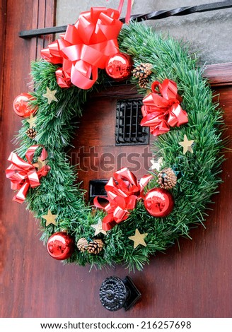 Christmas wreath with pine cones, red bows, balls and golden stars hanging on the wooden door. Greeting card. - stock photo
