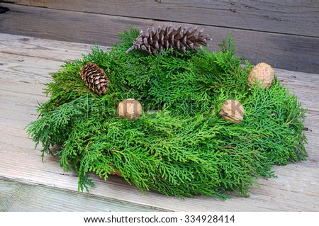 Christmas wreath with pinecones and walnuts on wooden table decoration - stock photo