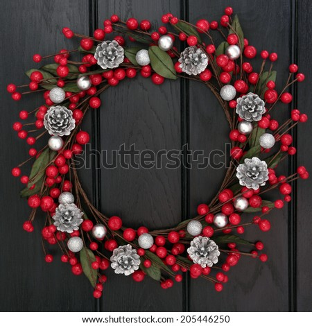 Christmas wreath with red and silver bauble decorations and pine cones over wooden background.