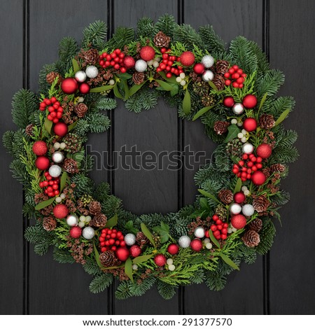 Christmas wreath with red and silver bauble decorations, holly, mistletoe and winter greenery over dark blue oak front door background.