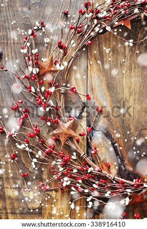 Christmas wreath with red and white berries and rusty metal stars on wooden background. Falling snow effect. Vintage Style - stock photo